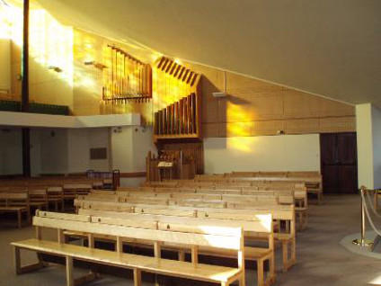 Image from inside the church showing the pews and organ