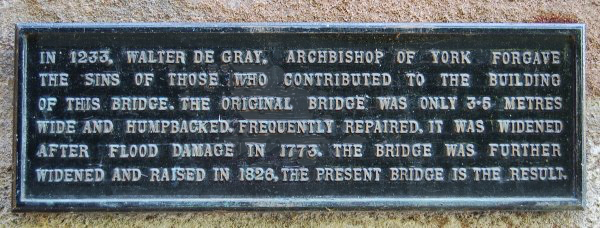 Plaque affixed to base of the bridge which reads: In 1233, Walter De Gray, Archbishop of York forgave the sins of those who contributed to the building of this bridge. The original bridge was only 3.5 metres wide and humpbacked. Frequently repaired, it was widened after flood damage in 1773. The bridge was further widened and raised in 1826, the present bridge is the result.