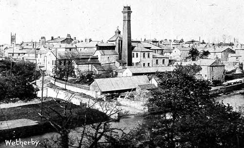View of Wetherby from the south of the River Wharfe, showing the building and chimney of Wharfedale Brewery (the chimney was demolished in 1937). The tower of St. James's Church can be seen in the background,left and the River Wharfe cuts across the foreground.