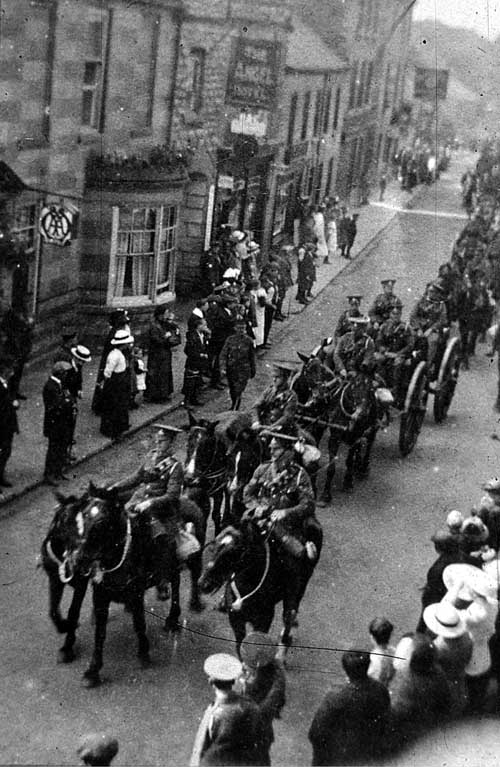 Image shows a parade down Wetherby High Street by the Coal Owners 155 West Riding Royal Field Brigade of Artillery, who were billeted in the Wharfedale Brewery during World War I. Visible in the background is the Angel Inn. The street is lined with people in period dress and it is recorded that the town council agreed to loan them the town band's instruments. The photograph is taken looking south.