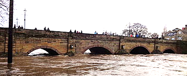 Photo of flood waters almost reaching pinnacle of the bridge arches.